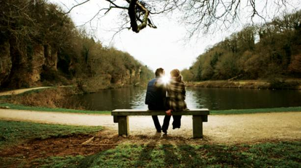 A couple on a romantic break sitting on a bench at Creswell Crags