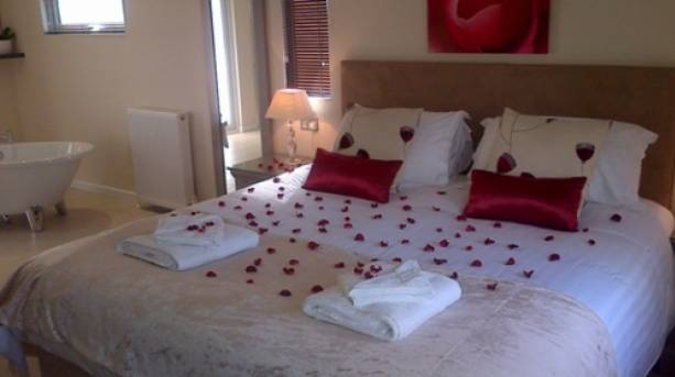 A bed covered in rose petals at Honeydale lodge in the Yorkshire Wolds