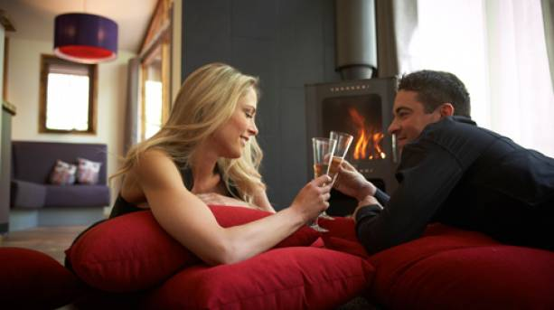A couple enjoying champagne in front of the fire