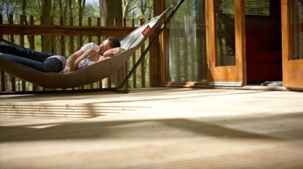 A couple lying in a hammock outside their forest cabin