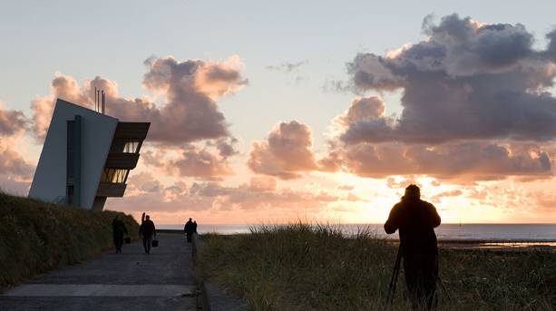 A photographer taking pictures of Rossall Tower at sunset