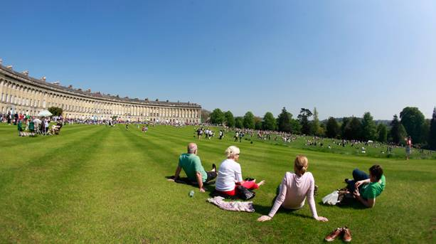 People sitting on the grounds of The Royal Crescent in summer