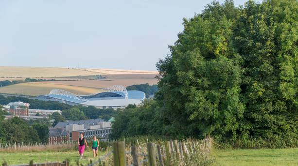 Two walkers with the Brighton Stadium in the background