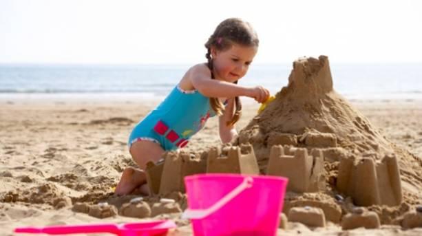 A little girl building a sandcastle
