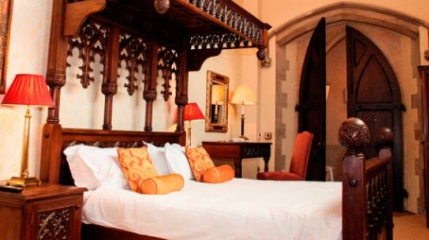 Old church doors open to a four poster bed