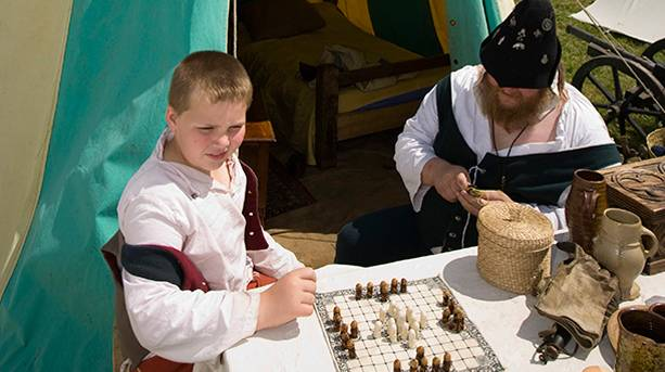 A man and a boy in costume playing chess