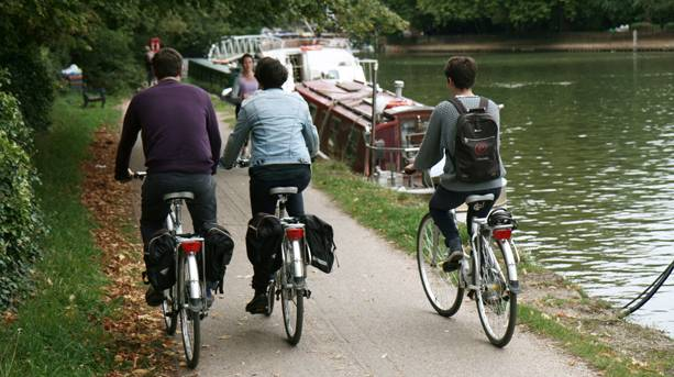 Three people cycling along the Thames