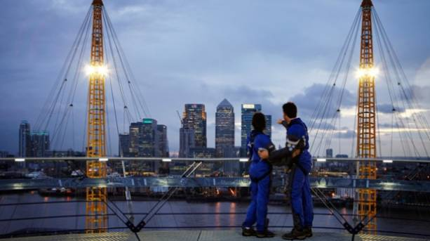 A couple wearing climbing gear admiring the view from the top of the o2