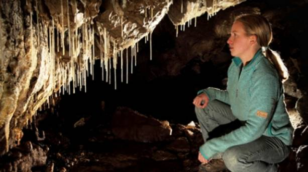 Visitor inspects stalagtites at Pooles Cavern, Peak District