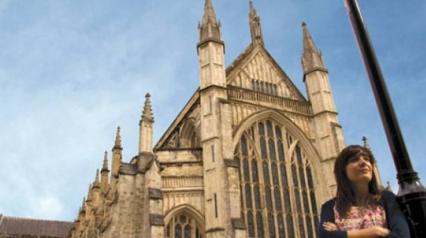 Tourist stands outside Winchester Cathedral
