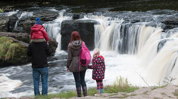 A family admiring Aysgarth Falls