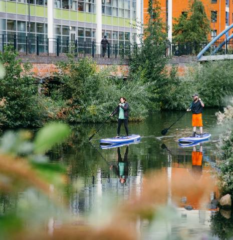 Two people stand-up paddleboarding through Sheffield