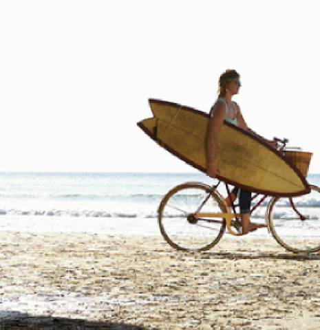 A woman cycles along a Cornish beach with her surfboard.