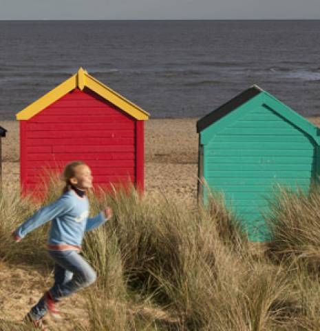 A family running along the beach in front of a row of beach huts.