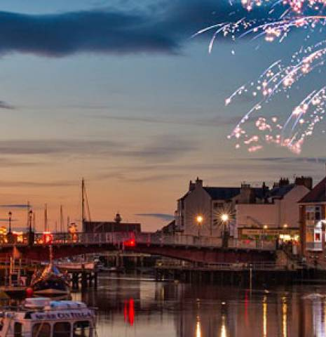 Whitby Regatta, the fireworks celebrations at night over the historic town of Whitby and the harbour, North Yorkshire, England.
