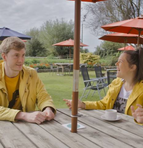 Rosie Jones and James Acaster sitting at pub garden table