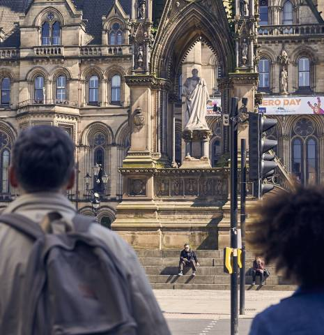 Manchester, England. A couple of visitors, man and woman hand in hand in front of the imposing Manchester Town Hall, a Neo-gothic Victorian municipal building designed by Alfred Waterhouse.