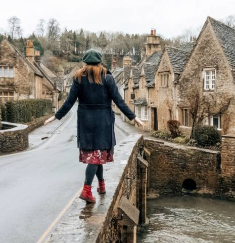 Girl walking along a bridge by a canal in Castle Combe, Wiltshire