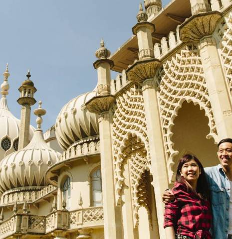 The Royal Pavilion, a former royal residence built in 1787, as a seaside retreat for George, Prince of Wales, Prince Regent. A Chinese couple, a man and woman walking through the grounds with the domes, lattice screens and minarets of the pavilion in the