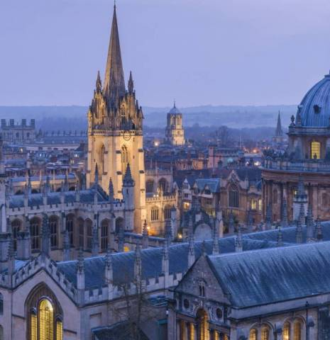 View from a height over the rooftops of Oxford city, the historic buildings and the landmarks of the university city. Night. Buildings lit up.