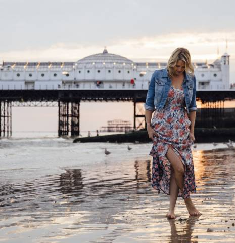 Woman standing on the beach near the illuminated Palace Pier at sunset, Brighton Beach and Pier, Brighton, East Sussex.