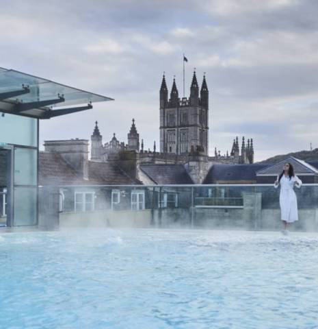 Woman wearing white toweling robe standing by the swimming pool, Thermae Bath Spa, Bath, Somerset, England.