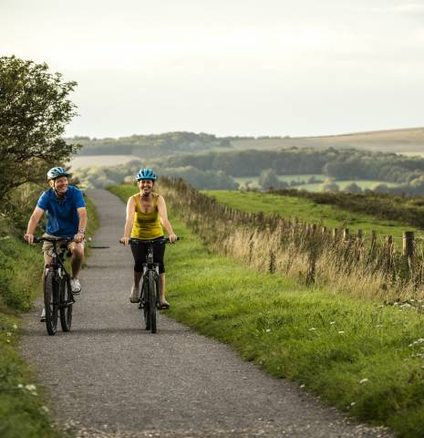 Two people cycling on a cycle path in the South Downs national park.