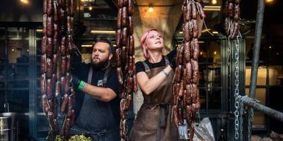 Man and woman cooking behind hanging sausages at Meatopia