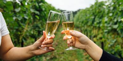Two people drinking wine at Bluebell Vineyard, East Sussex.