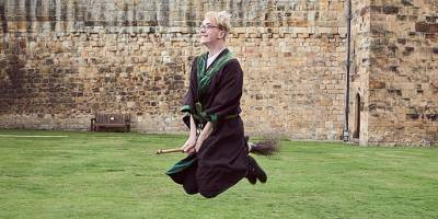 A man in Harry Potter dress riding a broomstick at Alnwick Castle.