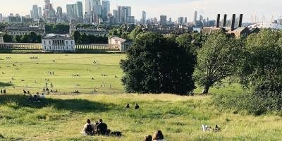 People sitting on the grass in Greenwich Park with a view of City skyscrapers in London, England