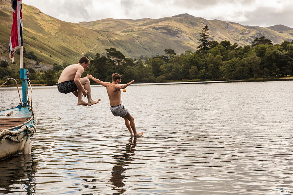 Two men in swimming shorts jumping off a boat into the lake at Ullswater, Lake District, Cumbria.