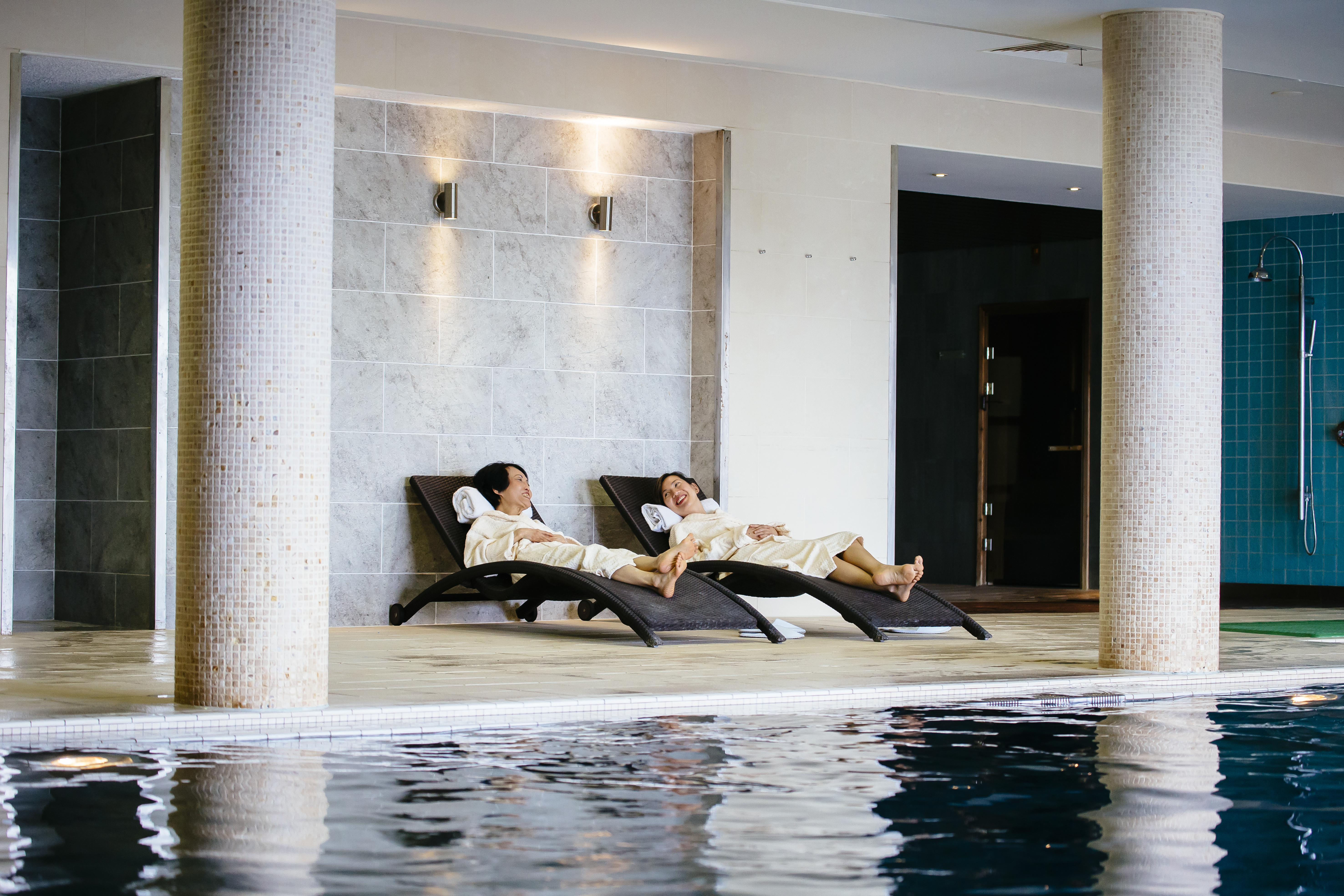 A Chinese mother and daughter relaxing by the indoor swimming pool
