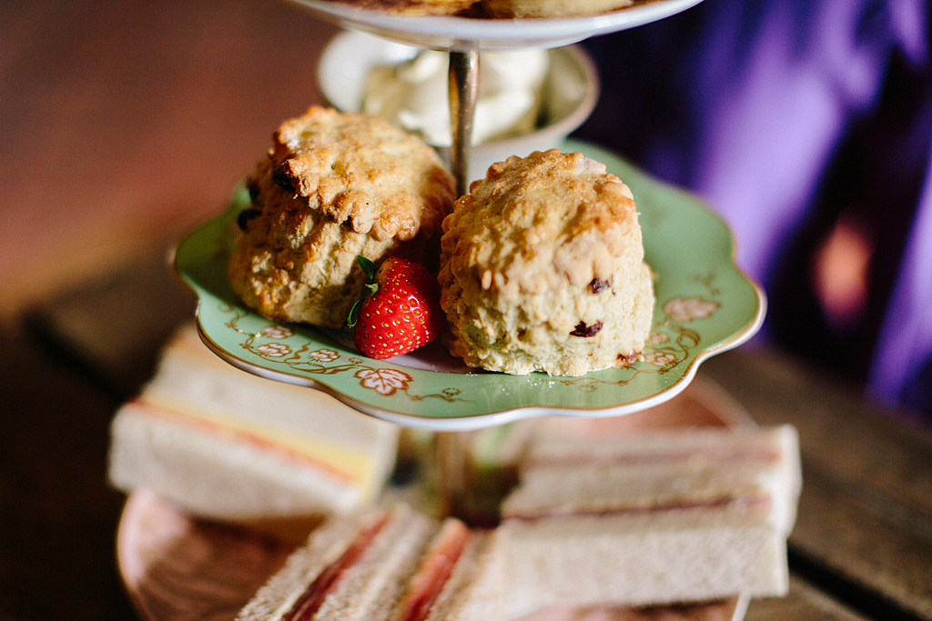 Afternoon tea at Leeds Castle near Maidstone, Kent, UK. A cake stand with a selection of foods.