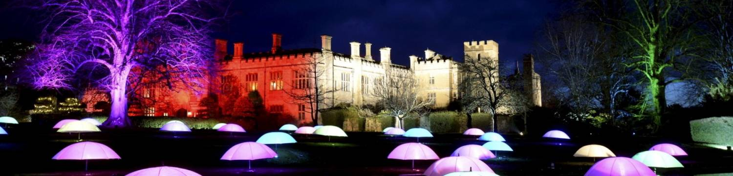 View of illuminations and lit up umbrellas in Spectacle of Light art installation at Sudeley Castle, Gloucestershire, England.