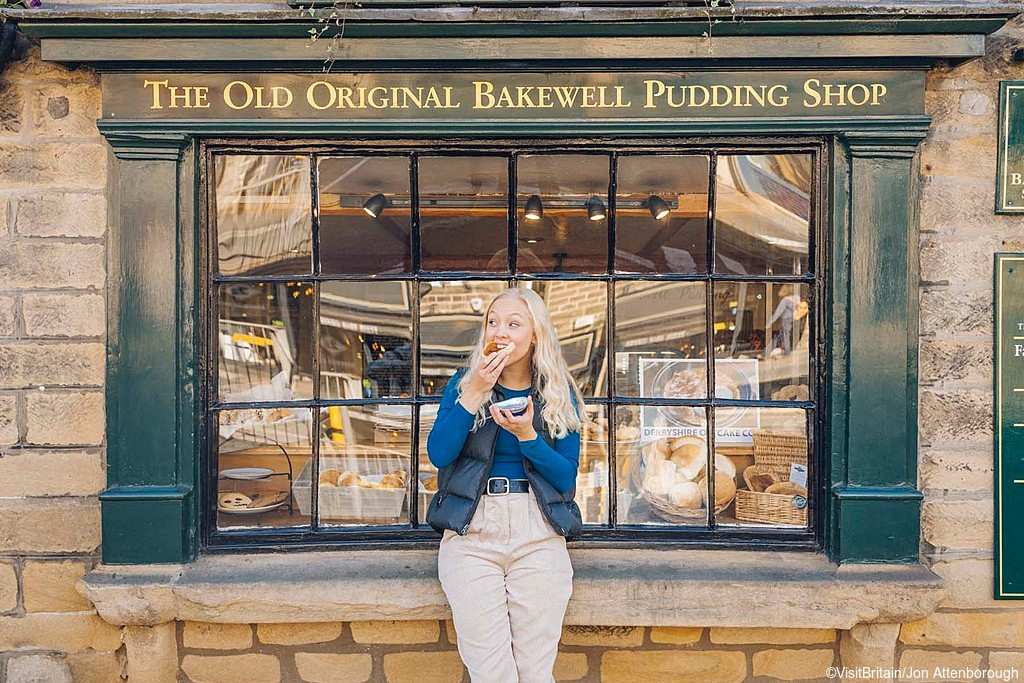 Woman eating in front of The Old Original Bakewell Pudding Shop, Bakewell, Peak District, Derbyshire, England.