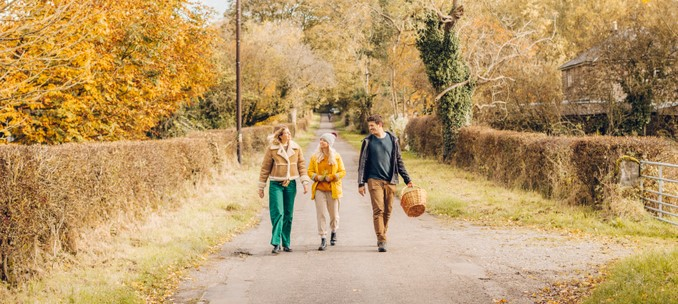 Two women and a man walking on a country lane in autumn on the Monsal trail, Peak District, Derbyshire, England.