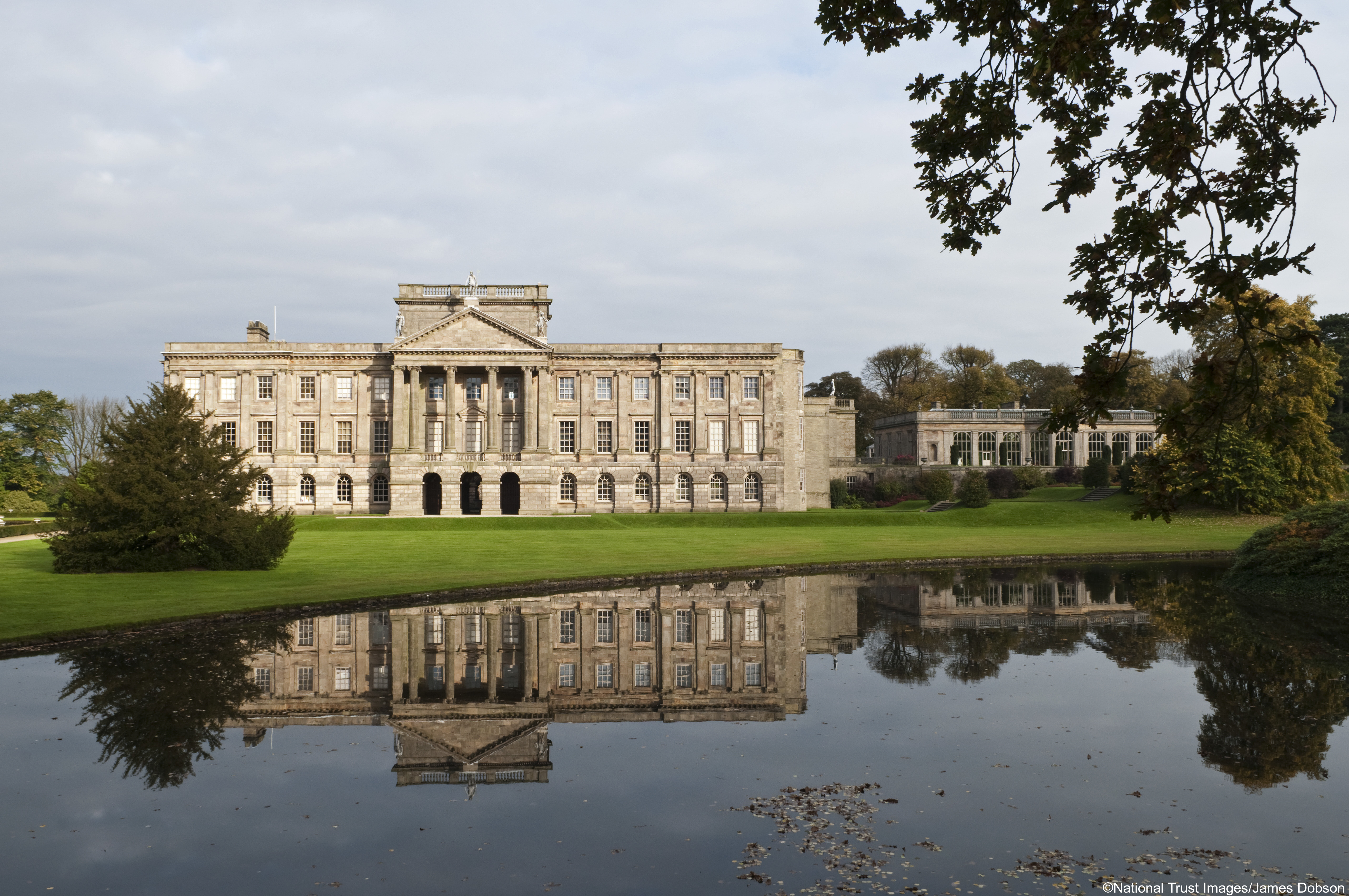 The south front of Lyme Park, Cheshire, seen across the lake, in autumn. The house was originally Elizabethan but was transformed in the Italianate style by architect Giacomo Leoni in the early eighteenth century.