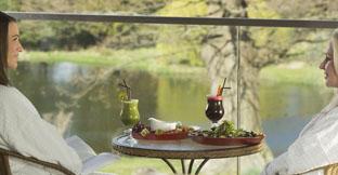 Two women having lunch in a spa garden