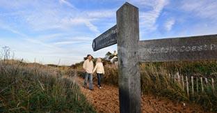 A couple walking around Norfolk Coastal Path
